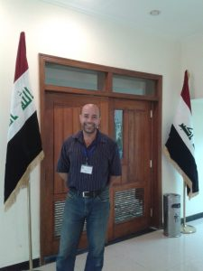 writer indoors in front of a door and flags